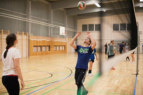 Zwei Studierende spielen Volleyball in der Sporthalle